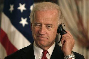 President Joseph Biden jamming a phallic device in his ear.