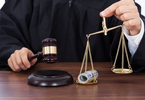Midsection of male judge striking gavel while holding scale with money in courtroom